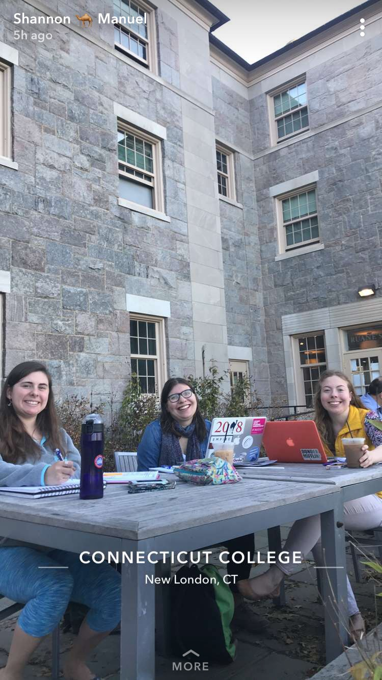 Julia and two other female students sit at tables outside of the Ruane's Den Coffee Closet doing school work.