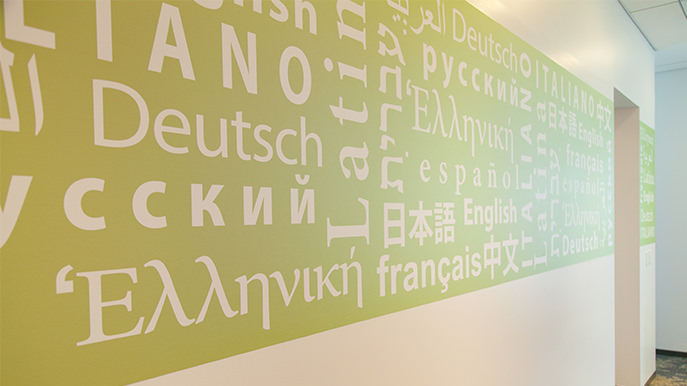 A wall with a lime green stripe and words written in different languages