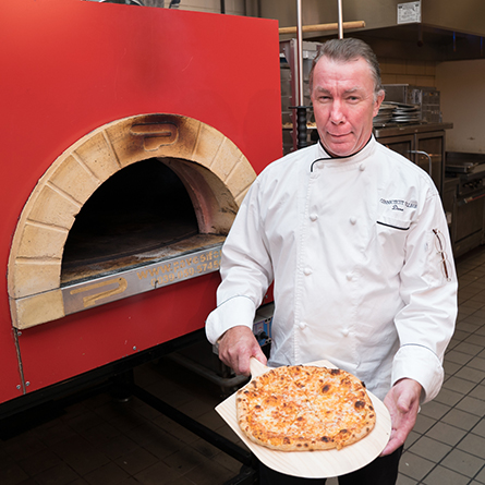 Chef Dave Perkins shows off a pizza made in the College's new pizza oven.